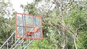 Las bolas se lanzan en el aro y la red de baloncesto Cámara lenta, árboles del fondo en un parque almacen de metraje de vídeo