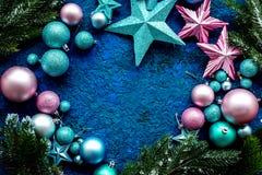 Las bolas y las estrellas enmarcan la maqueta para adornar el árbol de navidad en la opinión superior del fondo azul Fotografía de archivo libre de regalías