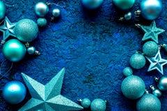 Las bolas y las estrellas enmarcan la maqueta para adornar el árbol de navidad en la opinión superior del fondo azul Imagen de archivo