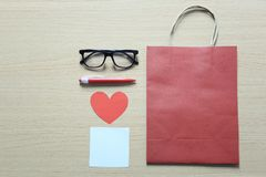 Las bolsas de papel y los accesorios rojos en el piso de madera y tienen copia Imagen de archivo