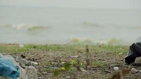 Las bolsas de plástico enormes de desperdicios en la orilla, gente que descuida peligros ambientales almacen de video