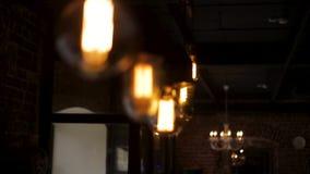 Las bombillas del estilo del vintage cuelgan y adornaron en una sala de estar El brillar intensamente ligero de lujo retro de la  almacen de video