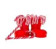 Las botas rojas de Santa Claus con las piruletas dulces coloreadas, caramelos, zapatos con el amarillo de la Feliz Navidad brilla Fotos de archivo libres de regalías