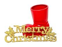 Las botas rojas de Santa Claus con las piruletas dulces coloreadas, caramelos, zapatos con el amarillo de la Feliz Navidad brilla Imágenes de archivo libres de regalías