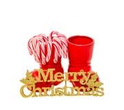 Las botas rojas de Santa Claus con las piruletas dulces coloreadas, caramelos, zapatos con el amarillo de la Feliz Navidad brilla Imagen de archivo