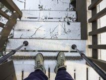 Las botas y los palillos del caminante en las escaleras con nieve Foto de archivo libre de regalías