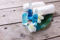 Las botellas con el aroma engrasan, las toallas y el plumeria tropical o de las flores Fotografía de archivo