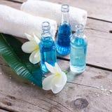 Las botellas con el aroma engrasan, las toallas y el plumeria tropical o de las flores Foto de archivo libre de regalías