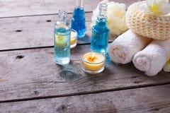 Las botellas con el aroma esencial engrasan, las toallas, las velas y las briznas Fotografía de archivo libre de regalías