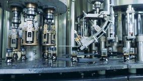Las botellas con el líquido están consiguiendo cubiertas con los casquillos por la máquina de la fábrica almacen de metraje de vídeo