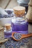 Las botellas de aceite esencial, cuchara de madera con lavanda seca florecen Imágenes de archivo libres de regalías