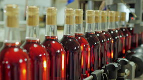 Las botellas de alcohol rojo están moviendo encendido la banda transportadora almacen de video