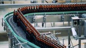 Las botellas de cerveza hechas del vidrio se están moviendo a lo largo de la banda transportadora metrajes