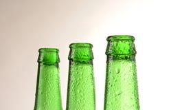 Las botellas de cerveza verdes calientan el fondo Foto de archivo