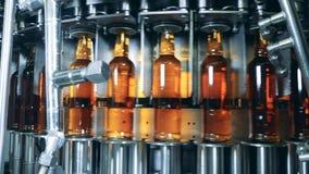 Las botellas de cristal con alcohol se están atando a un transportador móvil almacen de metraje de vídeo