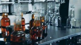 Las botellas de cristal con la bebida y las vacías se están moviendo a lo largo del transportador metrajes