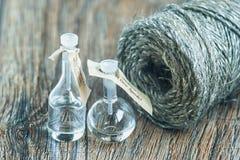 Las botellas de cristal en una superficie de madera con la madeja del yute trenzan imagen de archivo libre de regalías