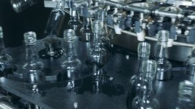 Las botellas de cristal están moviendo alrededor transportadores del metal almacen de metraje de vídeo