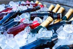 Las botellas de la bebida se refrescan en un buque grande con hielo fotos de archivo libres de regalías