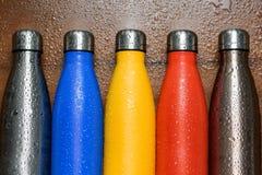 Las botellas de termo inoxidables coloridas en una tabla de madera rociaron con agua fotos de archivo