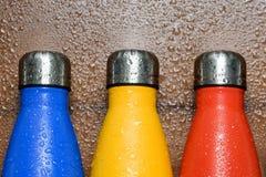Las botellas de termo inoxidables coloridas en una tabla de madera rociaron con agua imagen de archivo libre de regalías