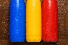 Las botellas de termo inoxidables coloridas en una tabla de madera rociaron con agua Foto de archivo libre de regalías