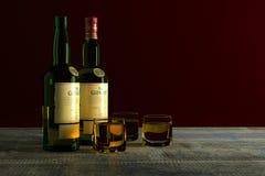 Las botellas de whisky de Glenlivet de 12 años con los vidrios llenaron w fotografía de archivo libre de regalías