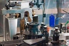 Las botellas en el transportador alinean como parte de la producción de la cerveza fotografía de archivo libre de regalías