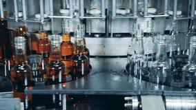 Las botellas hechas del vidrio están consiguiendo llenadas del líquido de consumición almacen de video