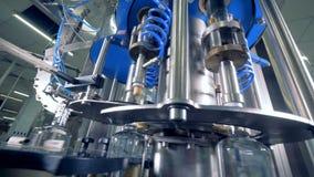 Las botellas móviles consiguen los casquillos en una planta, cierre para arriba Equipo industrial automatizado metrajes