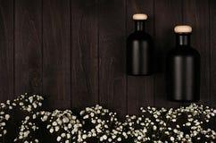 Las botellas negras en blanco de los cosméticos con las pequeñas flores blancas en tablero de madera oscuro, imitan para arriba,  Fotos de archivo libres de regalías