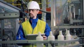 Las botellas plásticas abiertas están pasando por el empleado de sexo masculino de la fábrica almacen de video