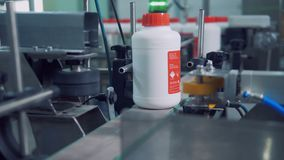 Las botellas plásticas etiquetadas se están moviendo a lo largo del transportador y están consiguiendo marcadas metrajes