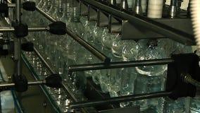Las botellas plásticas llenaron de agua en el transportador metrajes