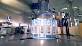 Las botellas se mueven en una línea, mientras que una máquina consigue códigos de barras listos para sellar 4K almacen de metraje de vídeo