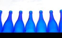 Las botellas vacías azules se alinearon en un contador foto de archivo