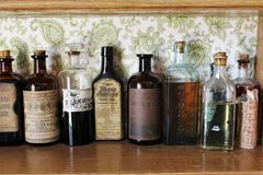 Las botellas viejas de la medicina en el estante en una droga pasada de moda hacen compras en el pueblo histórico de Sherbrooke e Imagen de archivo