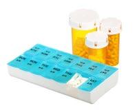 Las botellas y la medicina de píldora dosifican la caja aislada en el fondo blanco. Dosificación semanal de la medicación en dispe Imagen de archivo