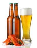 Las botellas y la taza de cerveza ligera y de langostas apilan   Imagen de archivo