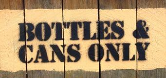 Las BOTELLAS y las LATAS firman SOLAMENTE el sello en el tablero de madera Foto de archivo libre de regalías