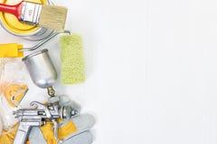 Las brochas, los rodillos, las latas de la pintura, los guantes y la pintura airbrush Fotos de archivo