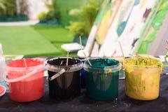 Las brochas usadas con la acuarela fijaron las latas viejas y los colores de la pintura Imágenes de archivo libres de regalías
