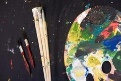 Las brochas usadas con la acuarela fijaron las latas viejas y los colores de la pintura Foto de archivo