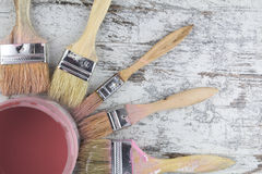 Las brochas y la pintura pueden en un fondo de madera Imagen de archivo libre de regalías