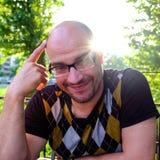 Las bromas de consumición de la sidra del hombre, sonrisas Un hombre joven bebe la sidra en un café abierto y miradas en la dista imagen de archivo libre de regalías