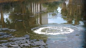 Las burbujas de aire enormes estallaron en la superficie del lago en el campo petrolífero metrajes