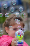 Las burbujas de jabón del pequeño niño que soplan con las burbujas disparan contra Imágenes de archivo libres de regalías