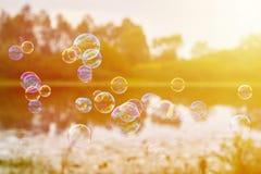 Las burbujas de jabón en los bancos del río vuelan viento abajo El concepto de ligereza y de viveza, luz del sol Foto de archivo