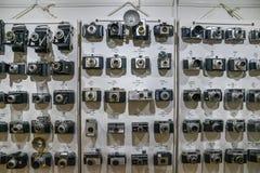 Las cámaras de la película del vintage se alinearon en la pared en orden cronológico que comenzaba a partir de 1920 s a mostrar d Foto de archivo