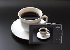 Las cámaras digitales compactas fotografiaron la taza de café. foto de archivo